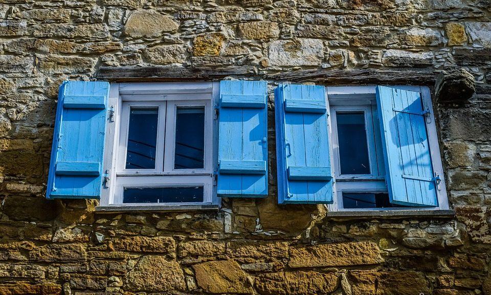 Vieilles fenêtres blanches aux volets bleus sur maison en pierre